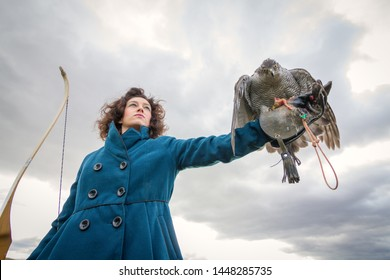 Female traditional archer with a Northern goshawk in her right hand.
