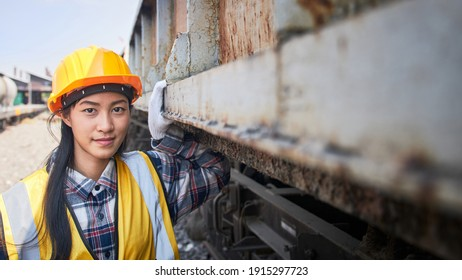 A female train maintenance engineer stands outdoors near a freight train waiting for a safety inspection, evaluation, and maintenance.