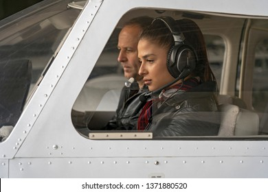 Female Trainee Pilot and Flight Instructor in an Aircraft Cockpit. Portrait of attractive woman trainee pilot with headset preparing to fly. She is sitting next to instructor and looking at dashboard.