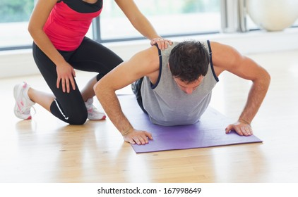 Female trainer assisting young man with push ups in the bright gym
