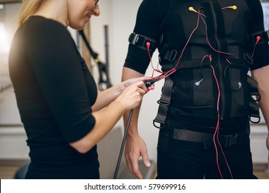 Female trainer connecting cables of ems suit