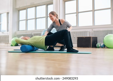Female trainer instructing senior woman going exercise on a foam roller. Elder woman doing pilates workout with personal instructor at gym.