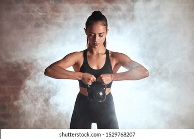 Female training biceps. Attractive sweaty fitness instructor in black sportswear posing with kettlebells. Steam background
