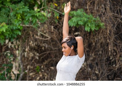 Female training at the park. Young woman warms up and stretches her arms outdoors in the morning. Healthcare, sport and exercise concept