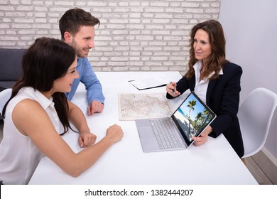 Female Travel Agent Giving Information To A Young Couple For Vacation Package