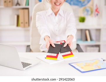 Female travel agent sitting at office and holding tickets. Close-up.