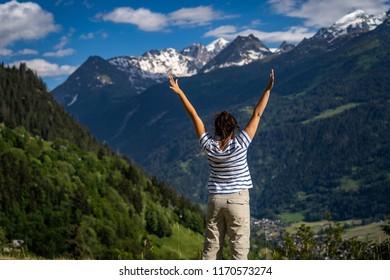 Female traveler admiring views of Swiss Alps in Val de Bagnes area, Switzerland.