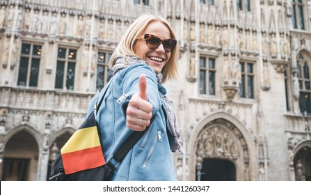 A female traveler with a backpack and a flag of Belgium stands on Grand Place Square in Brussels and shows her thumbs up, Belgium.