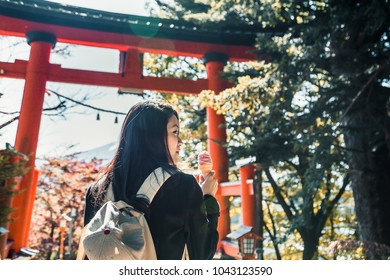 The female traveler is eating an ice-cream in front of the red Japanese shrine gate (Torii gate). Japanese spring season concept.