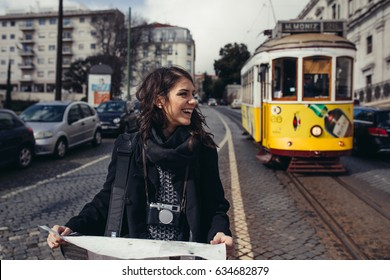 Female traveler holding and reading tourist map ,waiting the tram,using public transportation in foreign country.Tourist in Lisbon,Portugal awaiting iconic yellow tram.Urban tourism.Traveling Europe