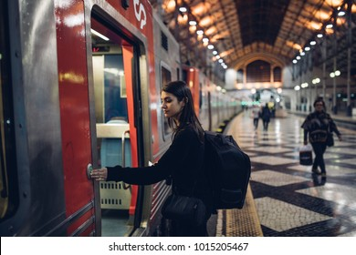 Female traveler holding the stop button on public transportation,being late for the train/tram,using transportation in foreign country.Urban tourism.Low budget cheap ticket backpacking.Traveling