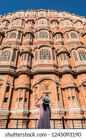 Female traveler look at the beautiful of Hawa Mahal, Palace of Wind is palace in Jaipur, India. It is constructed of red and pink stone.