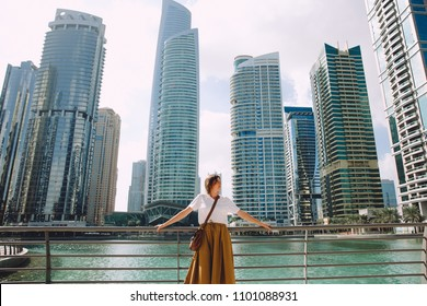 Female traveler looking at modern city architecture against blue sky, Dubai, UAE