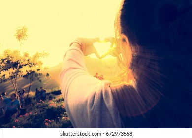 Female traveler make heart-shaped hand with sun. Love to travel.