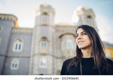 Female traveler on trip to Europe.Female tourist traveling around the world.Exited woman standing in front of historical landmark,Pena palace,famous attraction.