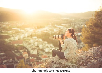 Female traveler photographer fascinated by illuminated nature at sunrise. Professional woman photographer taking outdoor portraits with telephoto lens. Taking break from job and enjoying the sunset.