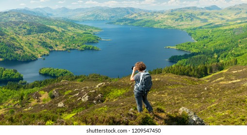 Female Traveler Photographer Taking Pictures on top of the Mountain in Ben A'an Hill, Highlands, Scotland - Landscape View From Ben A'an Hill, Highlands, Scotland