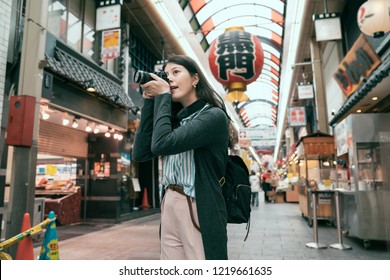 """female traveler photographing japanese local lifestyle traditional market in Japan. lens man tourist hobby love taking picture by slr camera. Translation of the lantern texting """"black gate""""."""