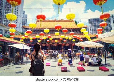 Female traveler photographing temples at Wong Tai Sin Temple Hong Kong landmark