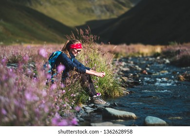 Female traveler resting in flowering meadow at flashy stream flowing in mountains valley in Caucasus, Georgia