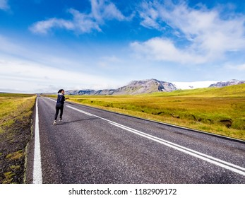 female traveler running into the horizon on the Ring Road in Iceland
