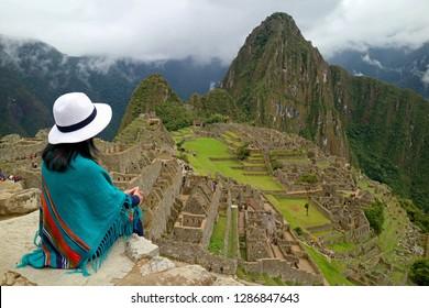 Female Traveler Sitting on the Cliff Looking at the Inca ruins of Machu Picchu, UNESCO World Heritage Site in Cusco Region, Urubamba Province, Peru