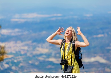 Female traveler stands on a hill, looks to the sky and scream from pleasure. Woman enjoying the views from the top of the mountain.