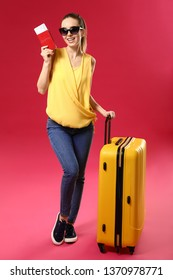 Female traveler with suitcase on color background