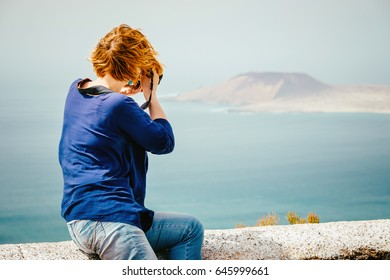 Female traveler taking a photo on the seaside
