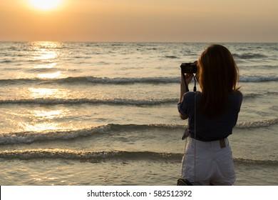 Female traveler taking a sunset photo on the beach.