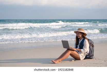 A female traveler using and working on laptop computer while sitting on the beach