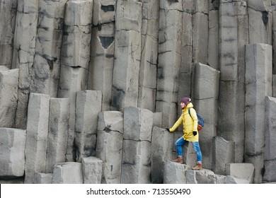 Female traveler walking on rocky formations at Reynisfjara Beach, Vik, Iceland