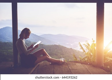Female traveler is watching video on digital tablet,while is sitting against amazing subtropical forest and sky background with copy space. Woman tourist is searching information on portable touch pad