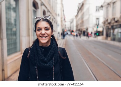 Female traveler woman walking streets of European capital.Visitor in Lisbon,Portugal.Traveling Europe on a budget.Studying abroad.Student discount for traveling concept