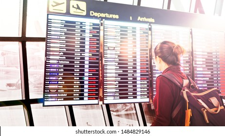Female travelers are checking the departures schedule at the airport,concept vacation travel in the summer