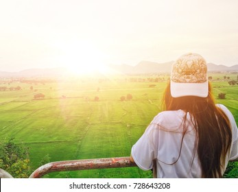 Female travelers stand watching the sunrise in the field.