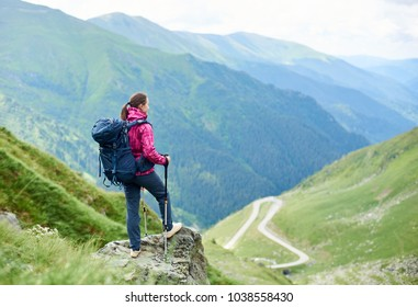 Female traveller with a backpack resting on top of a hill looking away at Transfagarasan road travelling Romania hiking backpacking tourism lifestyle memories harmony destinations active.