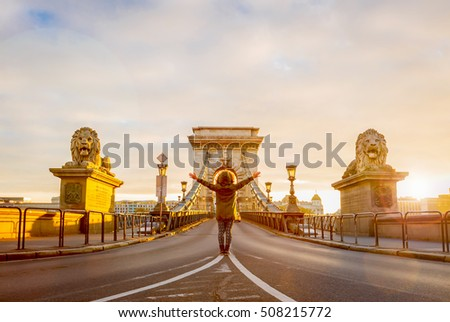 Female traveller stands in middle of chain bridge after sunrise in Budapest, bright sunlight and lens flare