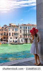 Female traveller woman enjoys the view to the architecture of the Canal Grande in Venice, Italy, on a sunny summer day