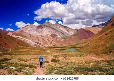 Female trekker walking alone on the trekking path to Aconcagua, highest peak in South America, Argentina