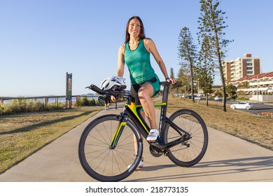Female triathlete with bicycle posing near the beach