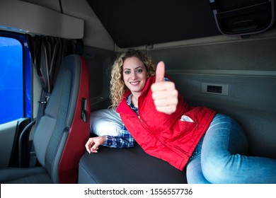 Female truck driver lying on vehicle cabin bed showing thumbs up. Woman professional commercial driver waking up in her bed fresh and ready to drive. Trucker lifestyle.