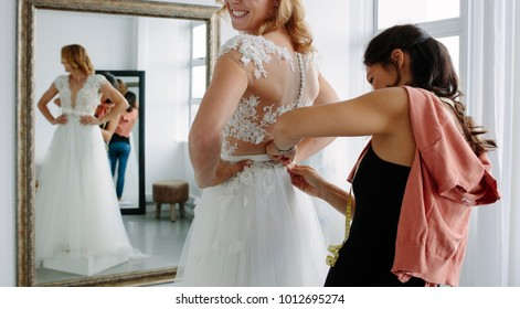 Female trying on wedding dress in a shop with women assistant. Female assisting bride getting dressed in wedding gown.