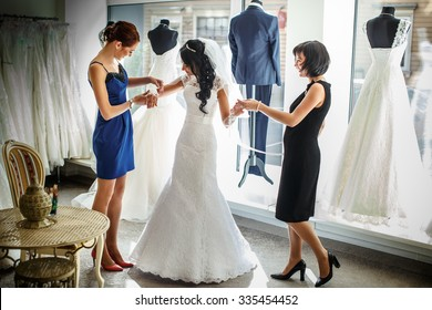 Female trying on wedding dress in a shop with two women assistants.