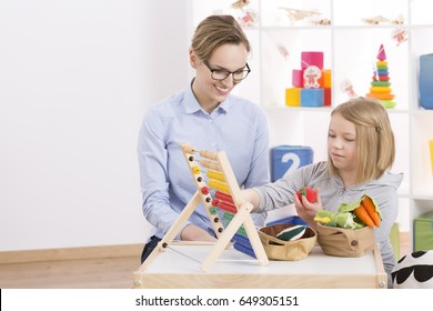 Female tutor and little girl counting with abacus in playroom