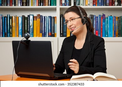 Female tutor or teacher with headset, computer and camera in her office talking with a student via video telephony, skype