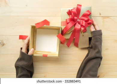 A female two hands opening the empty(blank) gift box on wooden table, top view.