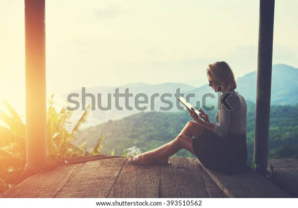Female is typing something in diary on touch pad, while is sitting against amazing Asian landscape in beautiful summer evening. Woman is watching video on digital tablet during her trip in Thailand