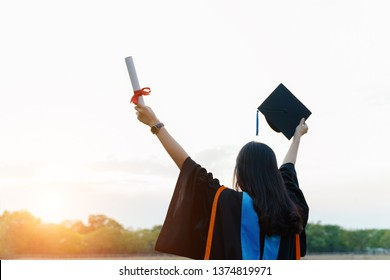 Female university graduate celebrates graduation ceremony receiving degree certificate happily with excitement.
