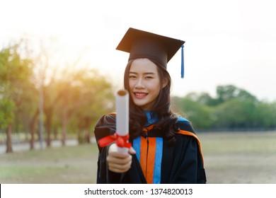 Female university graduate celebrates graduation ceremony receiving degree certificate happily with excitement.